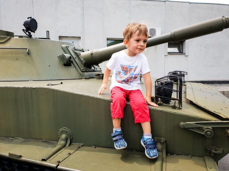 Bild des kleinen Kleinkindjungen, der auf Behälter am Militärweltkriegmuseum sitzt und klettert lizenzfreie stockbilder