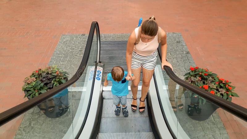 Bild des kleinen Kleinkindjungen, der eigenh?ndig seine Mutter bei der Stellung auf der Rolltreppe am Einkaufszentrum oder am Flu lizenzfreie stockfotografie