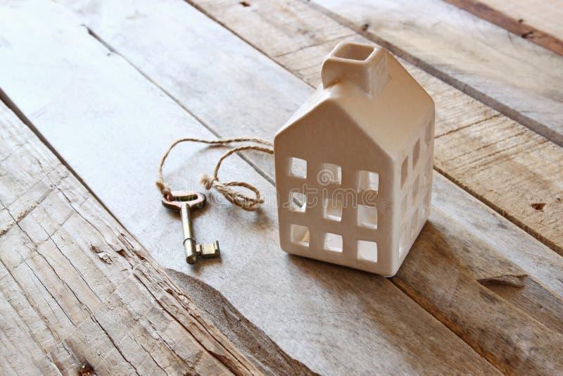Bild des kleinen Miniaturhauses und alter Schlüssel über rustikalem Holztisch stockfotografie