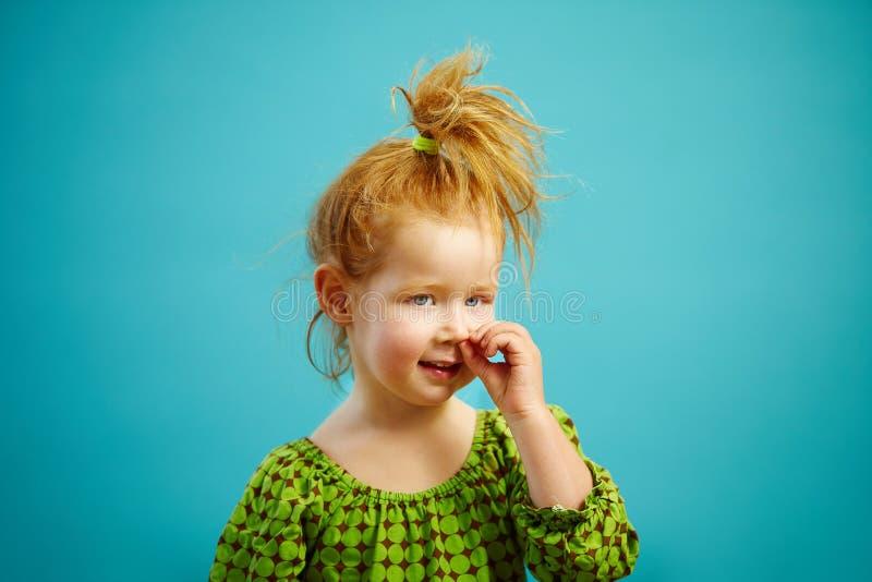 Bild des kleinen rothaarigen lustigen Mädchens wählt seine Nase aus, die auf blauem Hintergrund lokalisiert wird Helles Porträt d lizenzfreies stockbild