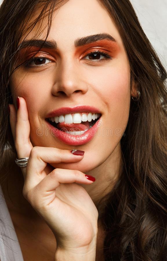 Bild des lächelnden Brunette mit hellem Make-up stockbild