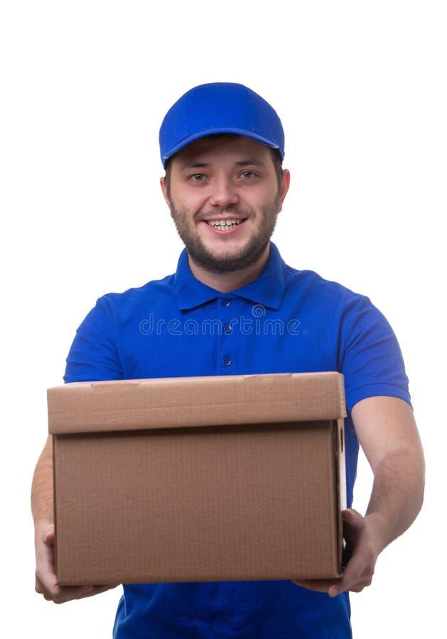 Bild des lächelnden Mannes im blauen T-Shirt und in der Baseballmütze mit Pappschachtel stockfotografie