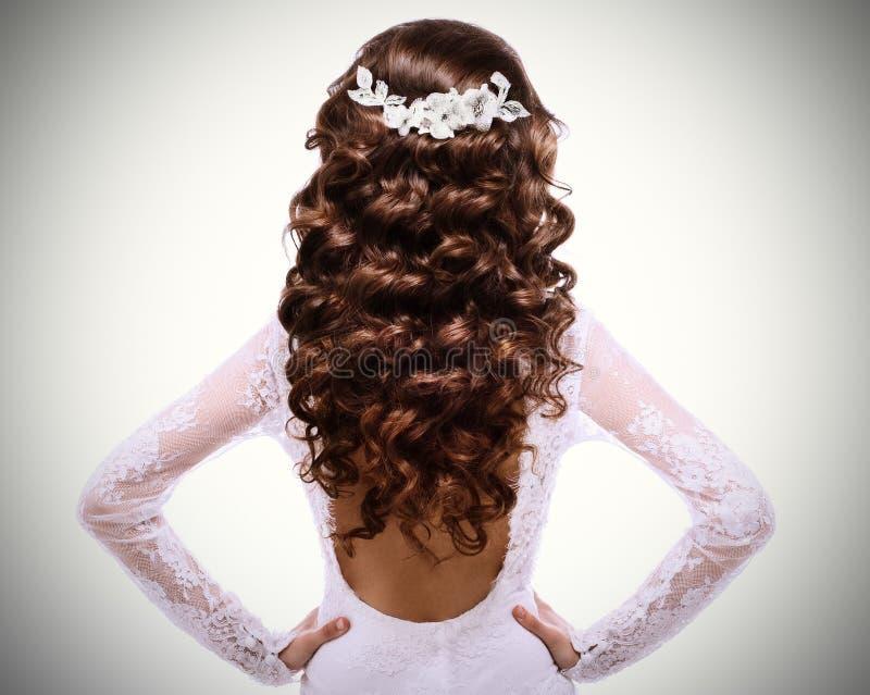 Bild des langen gelockten braunen Haares Brunettemädchen im weißen Hochzeitskleid mit einer tief ausgeschnittenen Rückseite stockbild