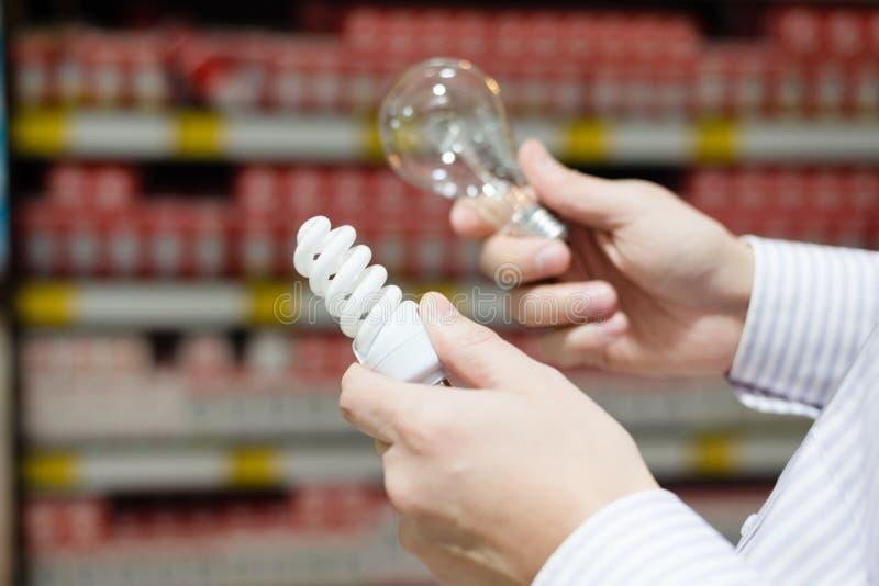 Bild des Mannes oder der Frau, die Wahl zwischen Energiesparender Leuchtstoff und Glühlampelampe des Weiß glühendfadens treffen stockbild