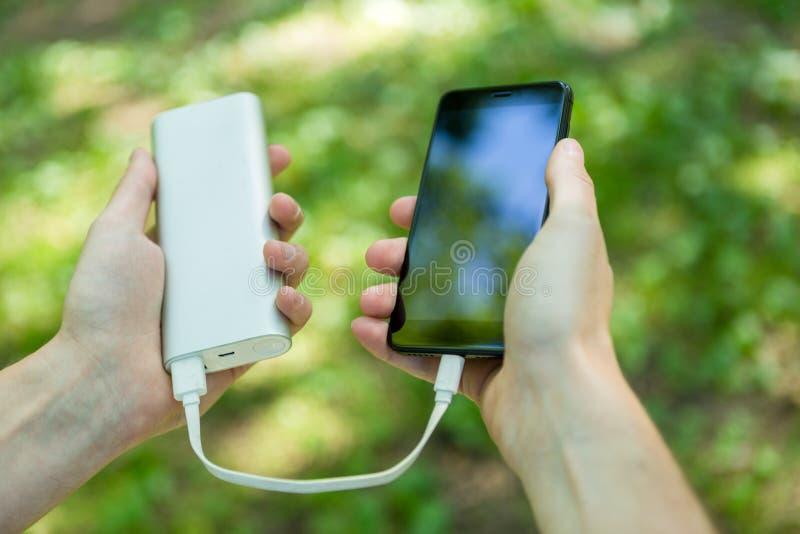 Bild des Mannes Telefon und powerbank halten lizenzfreies stockfoto