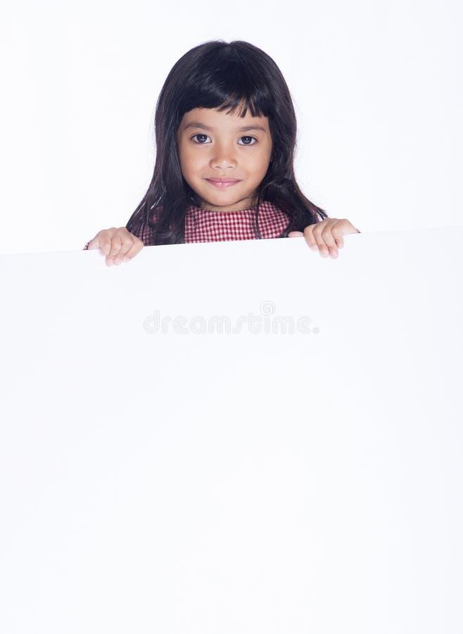 Bild des netten kleinen Mädchens, das leeres Weißbuch, lokalisiert auf Weiß hält lizenzfreies stockbild