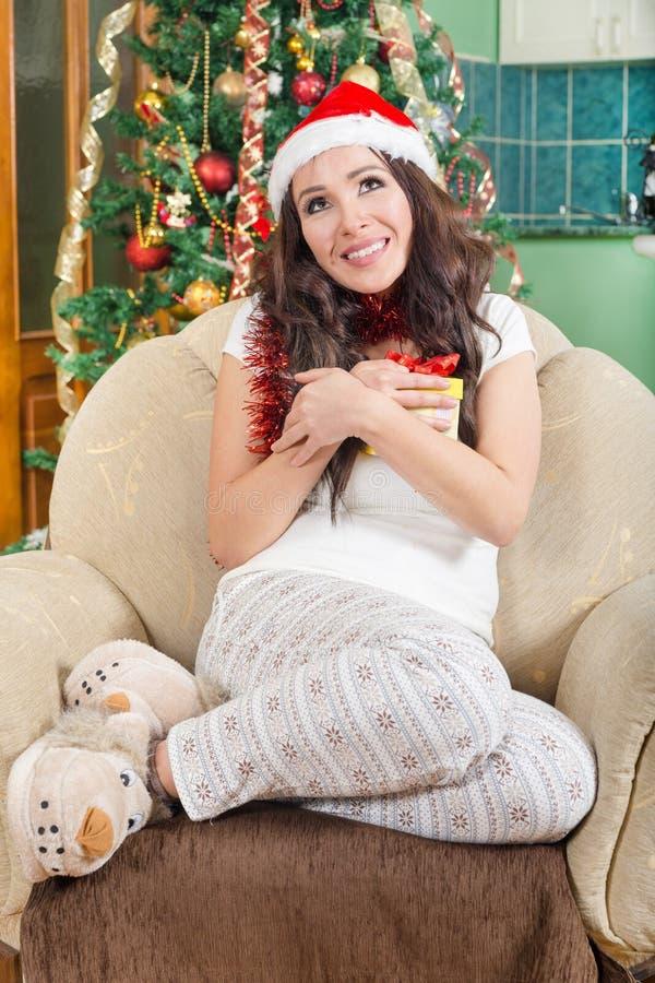Bild des netten Sankt-Helfermädchens mit dem Geschenkboxgenießen lizenzfreie stockfotografie