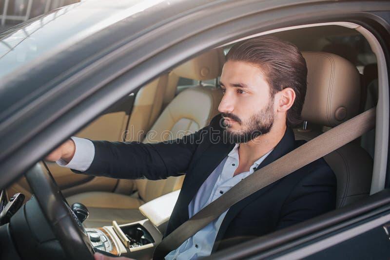 Bild des netten und überzeugten Geschäftsmannes, der im Luxusauto sitzt Er schaut direkt Mannhaltungen Er hat Sicherheitsgurt stockbild