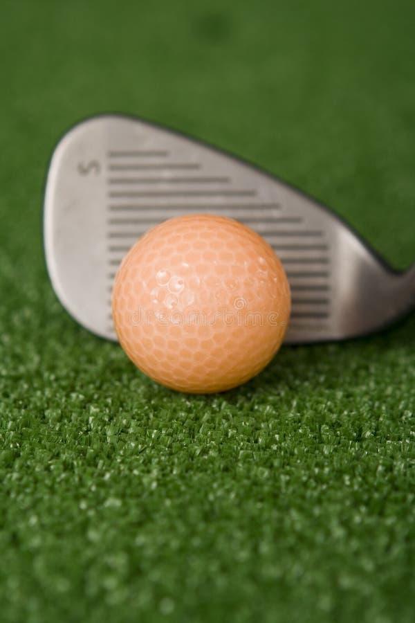Bild des orange Golfballs und des Sandeisens an der Adresse lizenzfreie stockfotografie