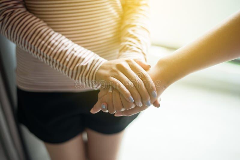 Bild des Paarfreundinnenh?ndchenhaltens und interessierenden Unterst?tzungszusammen tr?sten, Ermutigungskonzept stockfoto