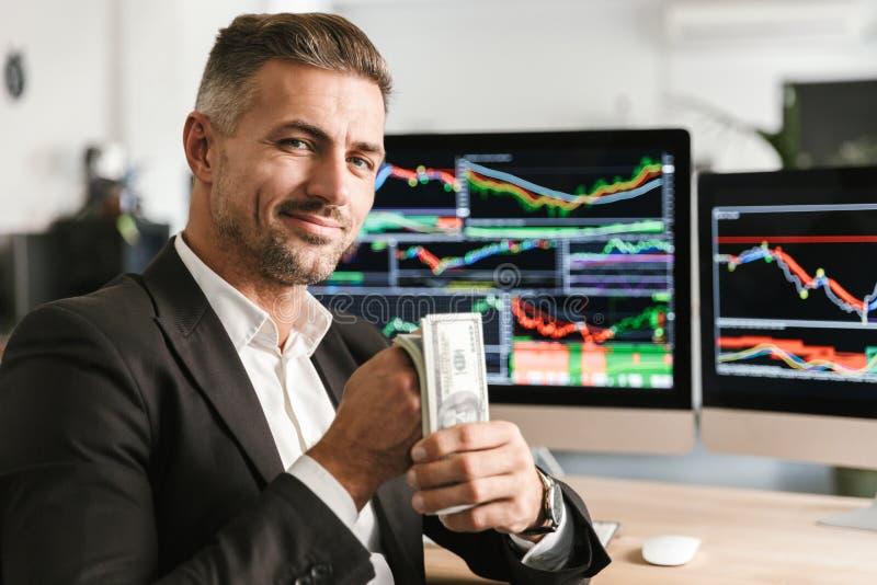 Bild des reichen Geschäftsmannholdingsatzes Geldes beim Arbeiten im Büro mit Grafiken und Diagrammen auf Computer stockbilder