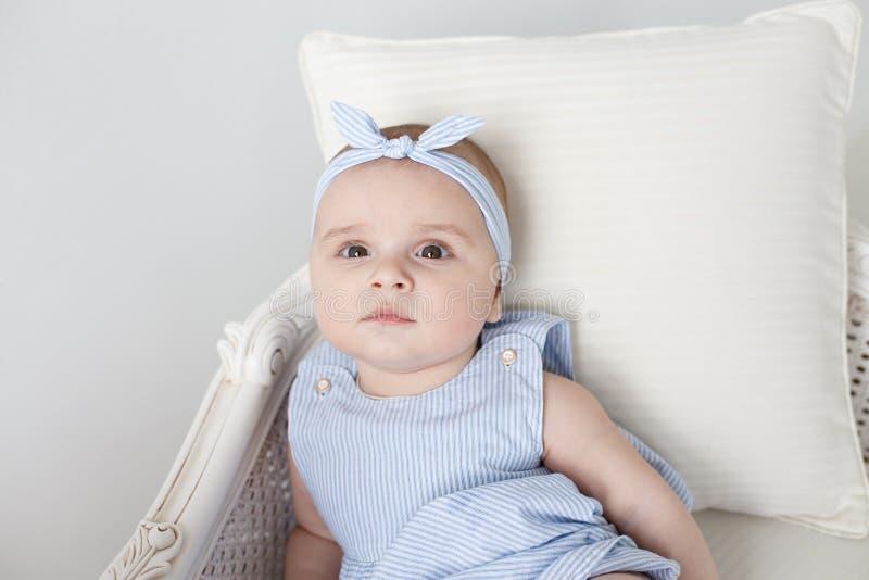 Bild des süßen Babys in einem Kranz, Nahaufnahmeporträt des lächelnden Mädchens des netten sechsmonatigen Babys, Kleinkind Blaues stockbild