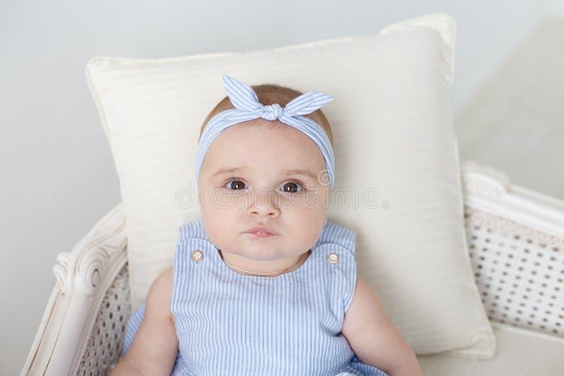 Bild des süßen Babys in einem Kranz, Nahaufnahmeporträt des lächelnden Mädchens des netten sechsmonatigen Babys, Kleinkind Blaues stockbilder