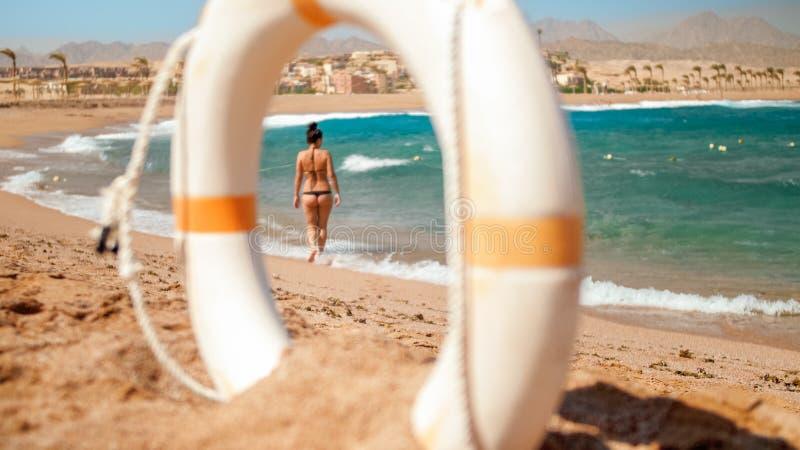 Bild des Schauens durch weißen Rettungsschwimmenplastikring auf sexy jungem owman im kleinen schwarzen Bikini, der auf den Strand lizenzfreies stockfoto
