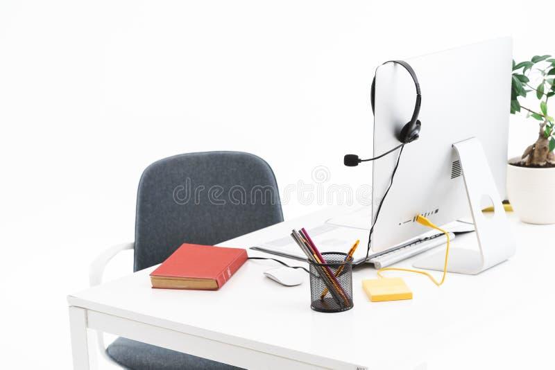 Bild des schwarzen Mikrofonkopfs für Helpline-Assistenz und eines im Büro befindlichen Silbercomputers stockfotos