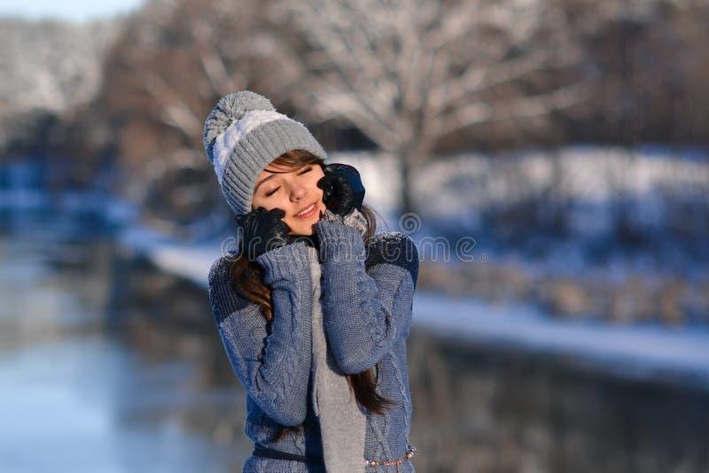 Bild des sonnigen lächelnden schönen netten Mädchens der geschlossenen Augen, das eine Winternatur auf schneebedecktem Hintergrun stockbilder