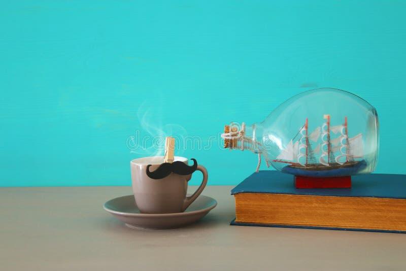 Bild des Tasse Kaffees, des alten Buches und des Bootes in der Flasche über Holztisch Vater ` s Tageskonzept lizenzfreie stockfotos