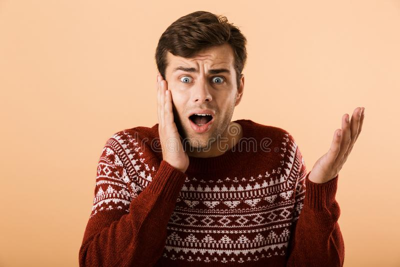 Bild des verwirrten Mannes 20s mit der Stoppel, die gestrickte Strickjacke s trägt stockfoto