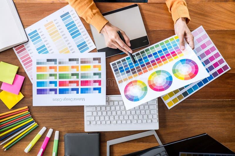 Bild des weiblichen kreativen Grafikdesigners, der an Farbauswahl arbeitet und auf Grafiktablette am Arbeitsplatz mit Arbeitswerk lizenzfreie stockbilder