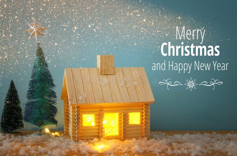 Bild des Weihnachtsbaums und des Holzhauses mit Licht durch das Fenster, über schneebedeckter Tabelle stockfotografie