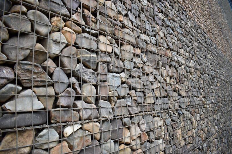 Bild einer Außenwand aus rohen Felsen, Steinen und mit dickem Metalldraht Es gibt eine sehr starke Struktur stockfoto