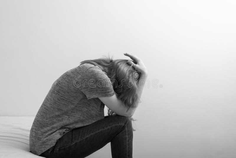 Bild einer Frau, die auf Bett in der Krise sitzt lizenzfreie stockfotos