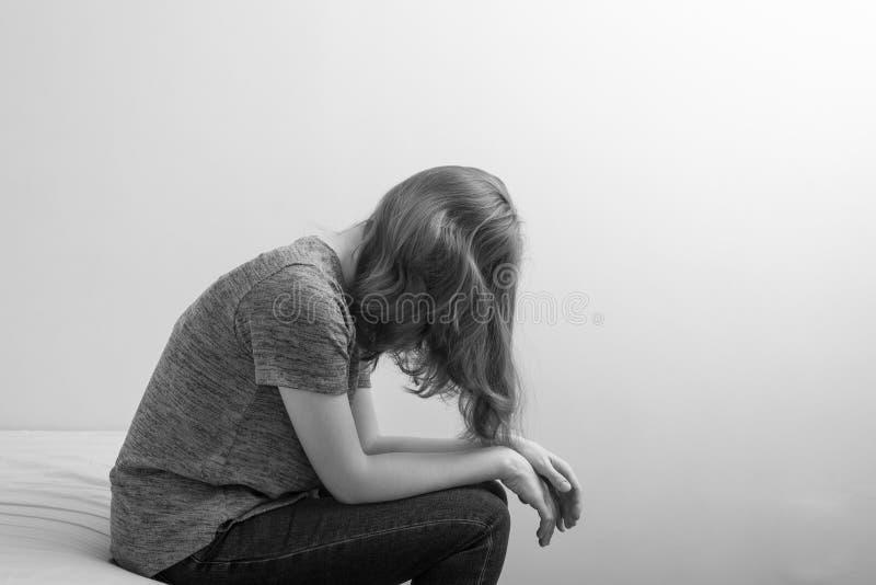 Bild einer Frau, die auf Bett in der Krise sitzt stockbilder