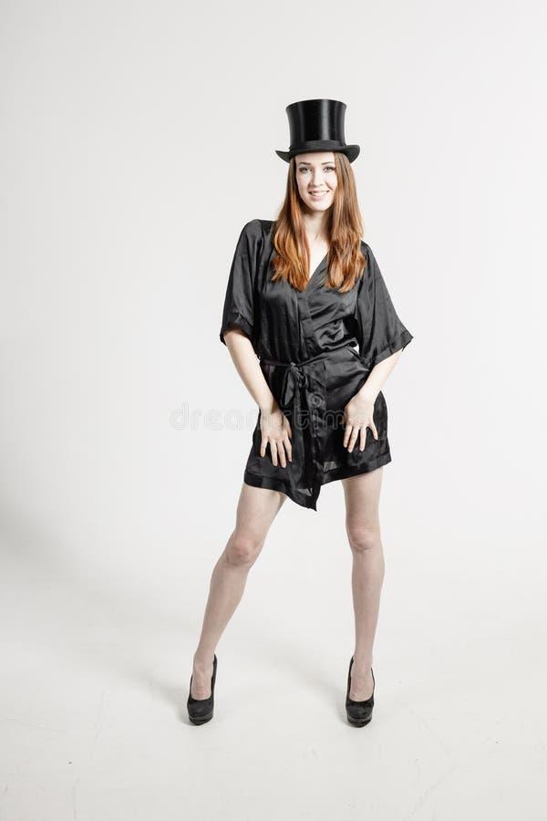 Bild einer jungen Frau in einem schwarzen Hausmantel und in einem Zylinderhut lizenzfreie stockfotos