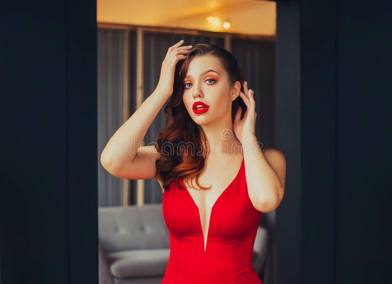 Bild einer jungen Geschäftsfrau bei einer formalen Glättungssitzung heller Lippenstift und Scharlachrot des Kleides, attraktives  lizenzfreies stockfoto