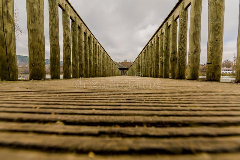 Bild einer Weise auf einer Holzbrücke, die zu einen Gazebo mitten in dem See führt stockfotografie