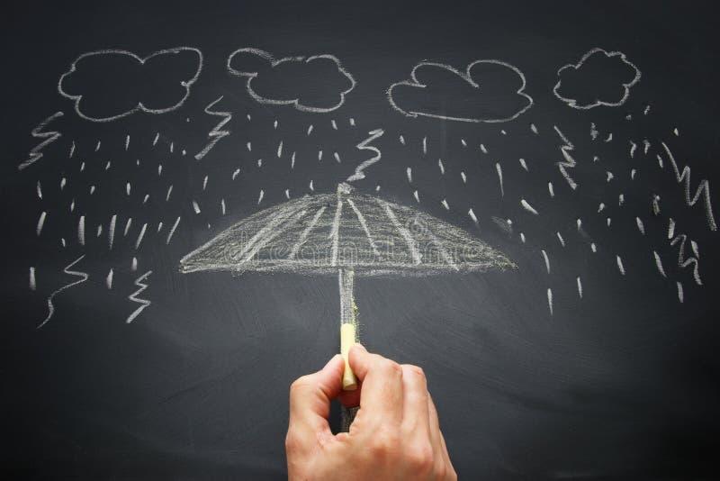Bild eines Mannes, der einen Regenschirm für Schutz gegen Regen und Sturm zeichnet Sicherheits- und Versicherungskonzept stockbilder