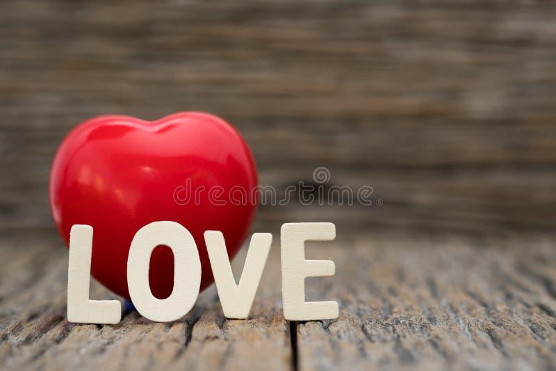 Bild-Enhjärta och förälskelseord på träbakgrund Dag för kopieringsutrymmevalentin royaltyfri bild