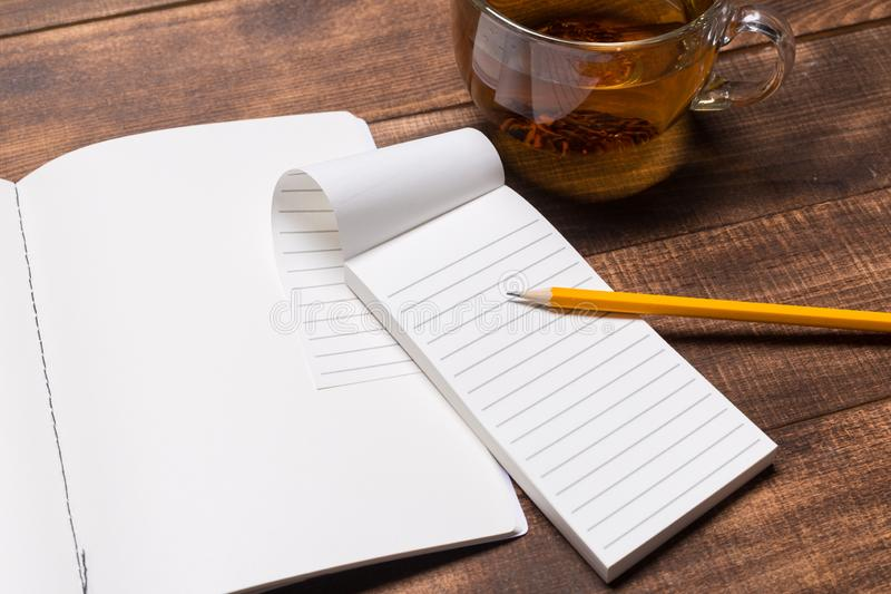 bild för bästa sikt av den öppna anteckningsboken med tomma sidor bredvid koppen kaffe på trätabellen Modell arkivbilder