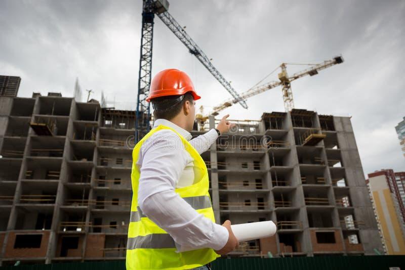 Bild för bakre sikt av den manliga arkitekten i hardhat som pekar på nybygge under konstruktion royaltyfria bilder