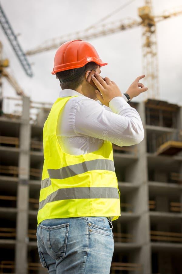 Bild för bakre sikt av den unga affärsmannen som talar vid telefonen på byggnadsplats och pekar på byggnad under konstruktion arkivbild