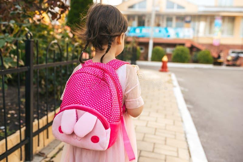 Bild för bakre sikt av gulligt gå för liten flickaförskolebarn som är utomhus- med den rosa ryggsäcken mot suddiga byggnader Lyck fotografering för bildbyråer