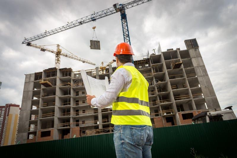 Bild för bakre sikt av konstruktionsteknikern i grön säkerhetsväst och röd hardhat som kontrollerar konstruktion av nybygge royaltyfria bilder