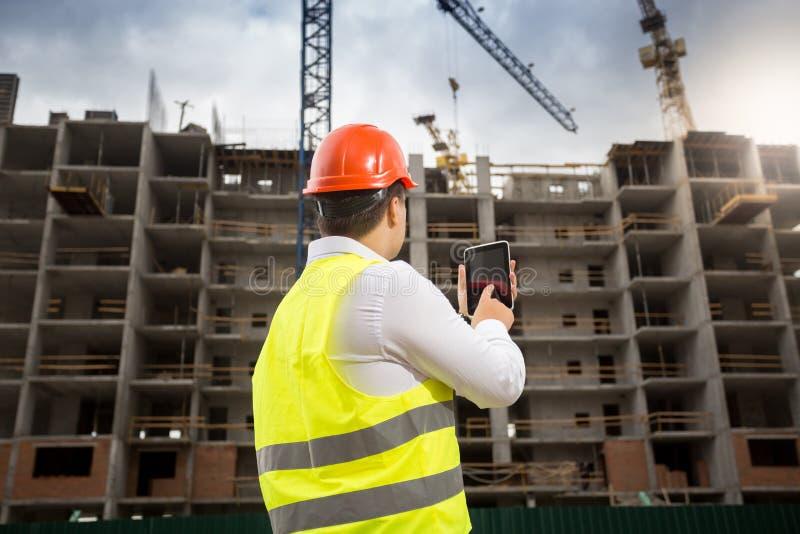 Bild för bakre sikt av konstruktionsteknikern som använder den digitala minnestavlan på byggnadsplats arkivbilder