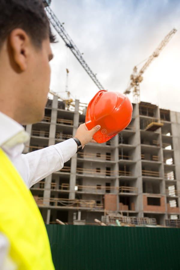 Bild för bakre sikt av konstruktionsteknikern som pekar på byggnadssi arkivbilder