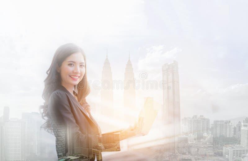 Bild för dubbel exponering av det lyckliga leendet för affärskvinna genom att använda bärbara datorn royaltyfria bilder