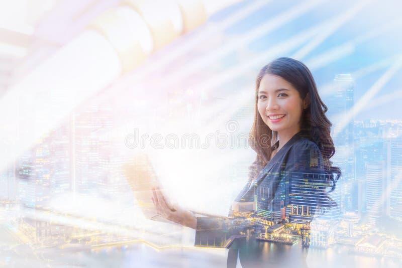 Bild för dubbel exponering av det lyckliga leendet för affärskvinna genom att använda bärbara datorn arkivbilder