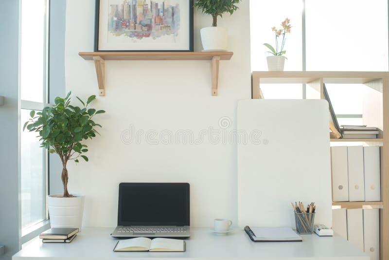 Bild för främre sikt av studioarbetsplatsen med den tomma anteckningsboken, bärbar dator Märkes- bekväm arbetstabell, inrikesdepa royaltyfri bild