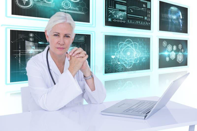 Bild för komposit 3d av ståenden av den säkra kvinnliga doktorn med bärbara datorn på skrivbordet arkivfoto