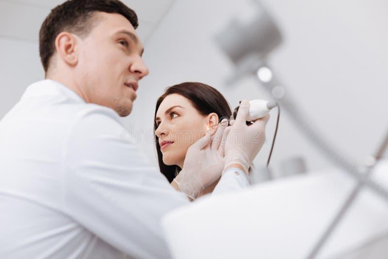 Bild för låg vinkel av den yrkesmässiga doktorn som kontrollerar det kvinnliga örat arkivfoton