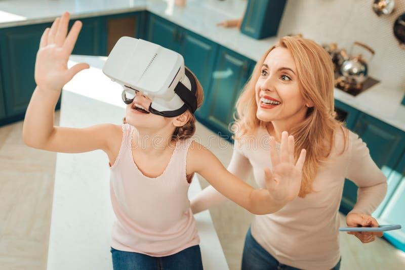 Bild för låg vinkel av mamman och ungen den testa VR-grej arkivfoton