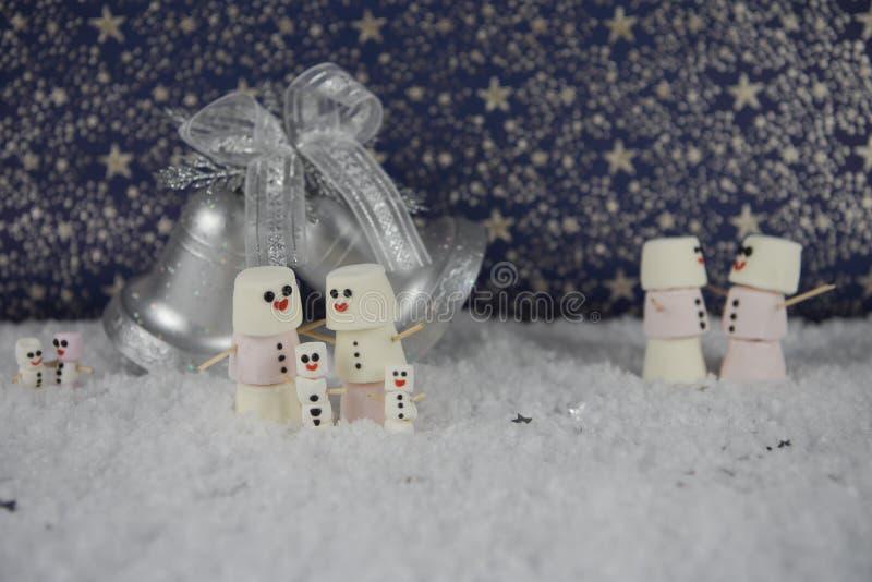 Bild för nytt år för jul av några marshmallower som formas som snögubben i snö med stjärnamodellen i bakgrund med klockagarnering royaltyfri bild