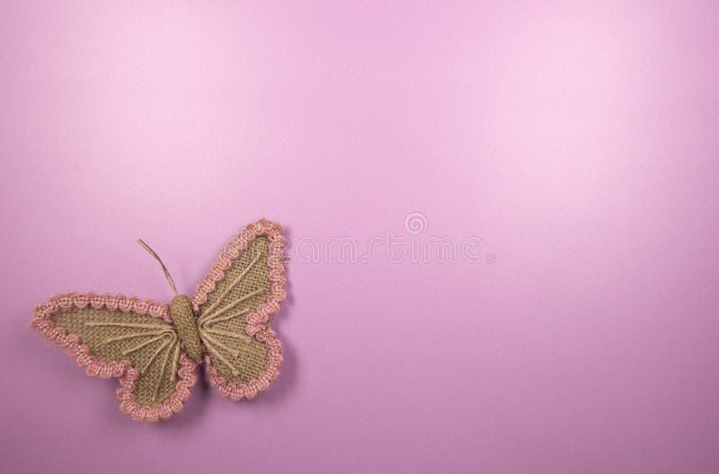 Bild för rosa färghantverkbakgrund av en fjäril royaltyfria bilder