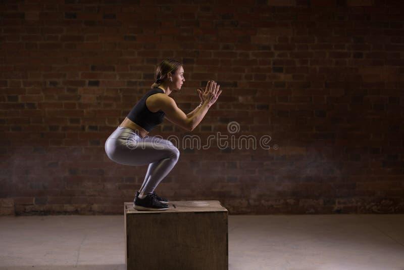 Bild för sidosikt av den unga kvinnan för passform som gör en askhoppövning arkivbilder