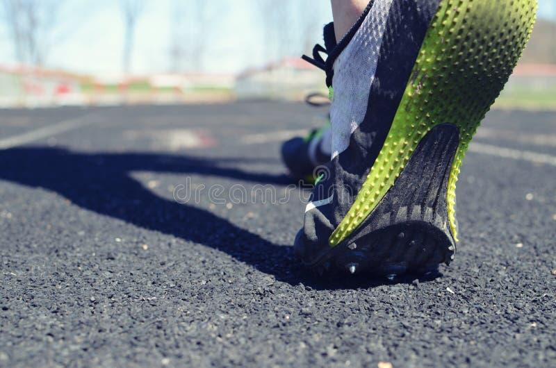 Bild för spåridrottsman nen, av personen som går på spår för övning i dagsljuset Visar gummi under fot och häckar i baksidan arkivbilder