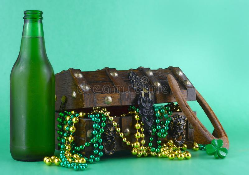 Bild för Sts Patrick dag på mars 17th Skattbröstkorg som symboliserar lycka och rikedom En flaska av öl och en hästsko tillfogade arkivbild